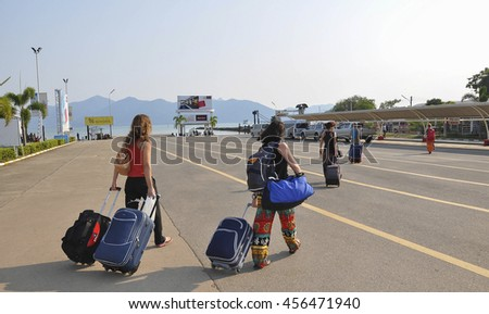 Koh Chang, Thailand - February 20, 2012: tourists with suitcases going to the pier, Thailand