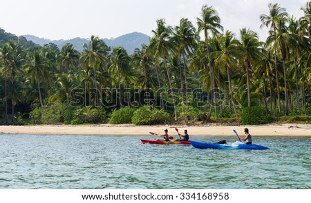 Koh Chang, Thailand MARCH 28, 2015; Tourists kayaking on sunny tropical beach with palm trees - stock photo