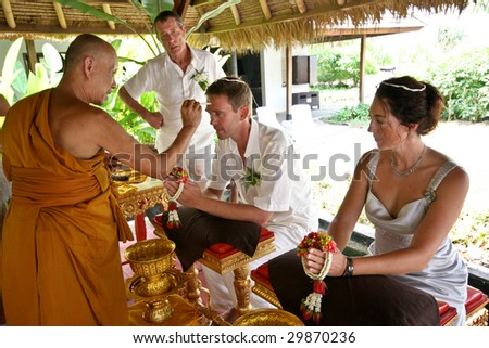 KOH LANTA - DECEMBER 2: Western couple gets married during a traditional Buddhist wedding on December 2, 2008 in Koh Lanta, Thailand. - stock photo