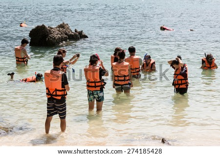 KOH LAO LA DING, KRABI, THAILAND - JANUARY 25: Group of young tourists learning to snorkel with safety life jackets on January 25, 2014 in Koh Lao La Ding, Krabi, Thailand
