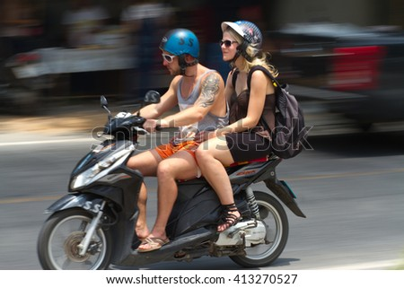 Koh Samui, Suratthani - April 30th, 2016 : Panning shot of Two tourists on motorbike wearing helmet in a sunny day on Koh Samui, Thailand,famous beach destination, the gulf of thailand
