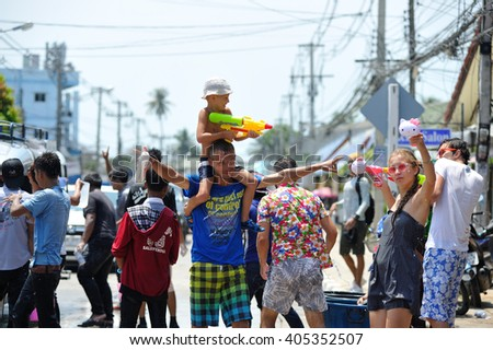 Koh Samui, Thailand - April 13, 2016: Thais and tourists and a little cute boy among them shooting water guns, pour water on each other, having fun at Songkran festival, the traditional Thai New Year