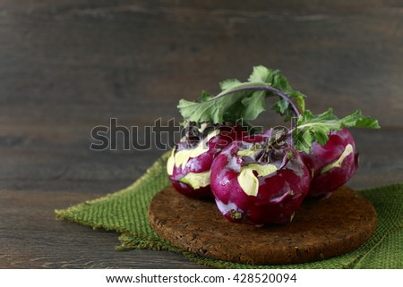 Kohlrabi cabbage with green leaves on wooden background