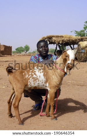 KOKEMNOURE, BURKINA FASO - FEBRUARY 23: A young farmer from the village of Kokemnoure is proud to be photographed with his goat, February 23, 2007. - stock photo