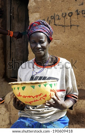 KOKEMNOURE, BURKINA FASO - FEBRUARY 21: Portrait of a woman, a resident of the village in Burkina Faso Kokemnoure poses with a traditional dish decorated, february 21, 2007. - stock photo