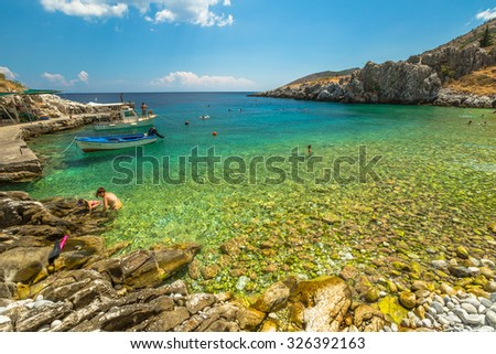 Kokkala Beach, Mania Peninsula, Lakonia, Peloponnese, Greece - August 23, 2015: tourists swim and sunbathe on a beautiful stone Kokkala beach with a transparent and turquoise sea.