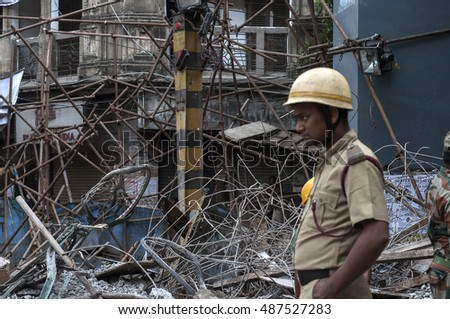 KOLKATA - APRIL 1: A cop passing by the portion of the fallen debris during the rescue effort after an under construction flyover collapsed killing 27 people on April 1, 2016 in Kolkata, India.
