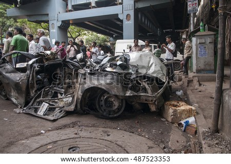 "KOLKATA - APRIL 1: People thronging an almost ""sandwiched"" private vehicle  during the rescue effort after an under construction flyover collapsed killing 27 people on April 1, 2016 in Kolkata, India."