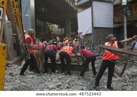 KOLKATA - APRIL 1: Workers picking up residual iron plates during the rescue effort after an under construction flyover collapsed killing 27 people on April 1, 2016 in Kolkata, India.