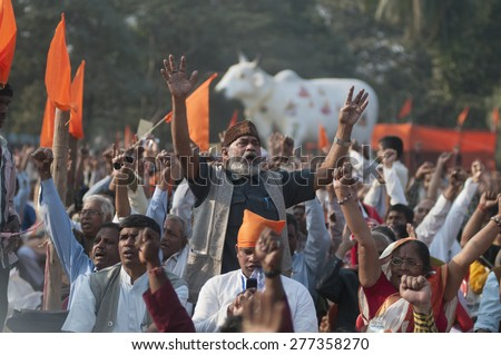 KOLKATA - DECEMBER 20:  A man chanting songs  with a dummy cow in the background during the Golden Jubilee celebration of VHP - a Hindu nationalist organization on December 20, 2014 in Kolkata,India.  - stock photo