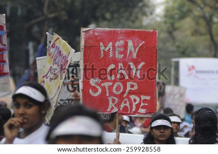 """KOLKATA - DECEMBER 16 : A woman holding a banner saying """" men can stop rape"""" during a rally to remember the gang raped victim from New Delhi in the year 2012 - on December 16, 2014 in Kolkata , India. - stock photo"""