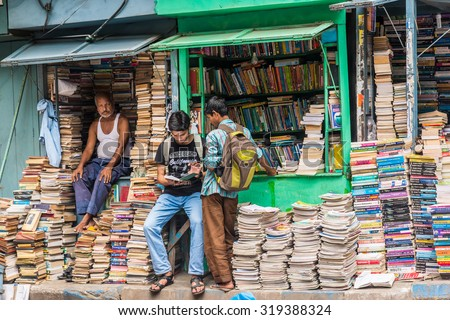 KOLKATA, INDIA - AUGUST 22: Unidentified students check out books at an old street side book stall on August 22, 2015 at College Street Book Market in Kolkata, West Bengal, India. - stock photo