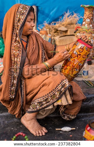 KOLKATA, INDIA - DECEMBER 7: An Indian craftswoman creates colorful handicraft items for sale during the annual State Handicrafts Expo 2014 on December 7, 2014 in Kolkata, West Bengal, India. - stock photo