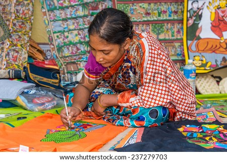 KOLKATA; INDIA - DECEMBER 11: An Indian craftswoman paints on colorful handicraft items for sale during the annual State Handicrafts Expo 2014 on December 11; 2014 in Kolkata; West Bengal; India.