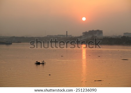 KOLKATA, INDIA - FEB 08: A boat crossing the river Ganges (aka River Hoogly) during sunset on February 08, 2014 - stock photo