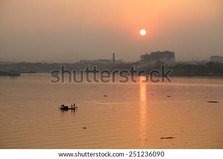 KOLKATA, INDIA - FEB 08: A boat crossing the river Ganges (aka River Hoogly) during sunset on February 08, 2014 - stock photo