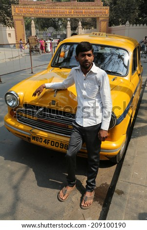 KOLKATA, INDIA - FEBRUARY 14: Indian taxi driver posing in front of his cab in Kolkata on February 14, 2014. The car is Hindustan Ambassador, manufactured since 1958. - stock photo