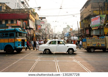 KOLKATA, INDIA - JAN 13: Antique white Ambassador car down the busy street on January 13, 2013 in Kolkata, India. First Ambassador was produced by the Yellow Cab Manufacturing Company in 1921 - stock photo