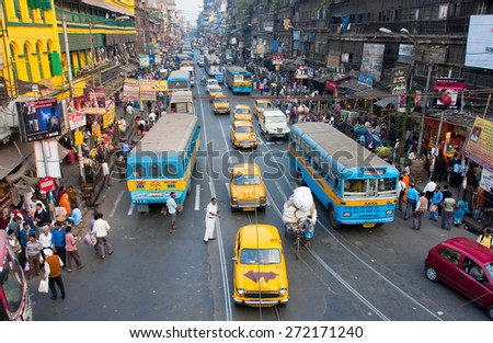 KOLKATA, INDIA - JAN 13: Antique yellow Ambassador taxi cabs down the busy street on January 13, 2013 in West Bengal. First Ambassador was produced by the Yellow Cab Manufacturing Company in 1921 - stock photo