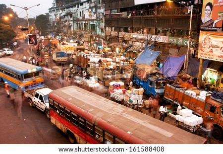 KOLKATA, INDIA - JAN 17: Blured in motion busy street with cars, buses and people traffic at evening on January 17, 2013 in Kolkata, India. Kolkata has a density of 814.80 vehicles per km road length  - stock photo