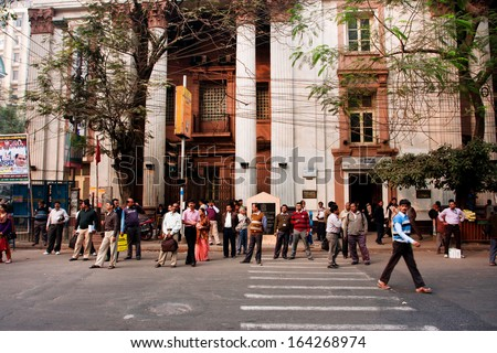 KOLKATA, INDIA - JAN 13: Pedestrians in a crosswalk waiting for the moment to cross the road on January 13, 2013 in Kolkata, India.  Kolkata metropolitan area is spread over 1,886.67 km2. - stock photo