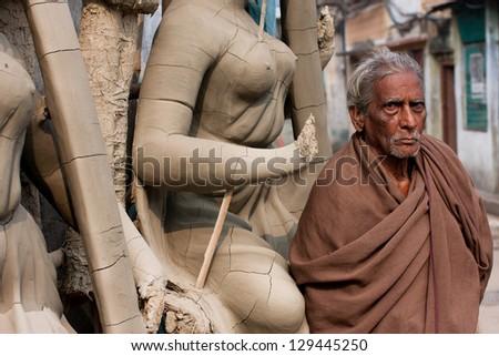 KOLKATA, INDIA - JAN 15: Senior asian man stands near the woman sculpture at Kumartuli artistic area on January 15, 2012 in Kolkata India. Populat. of Kolkata is 4.5 million out, 2,5 million are males - stock photo