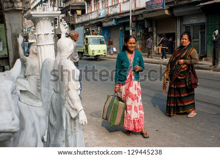 KOLKATA, INDIA - JAN 15: Senior asian women wait for the transport at sculpture masters street on January 15, 2012 in Kolkata, India. Population of Kolkata is 4.5 million out, 2 million are females - stock photo