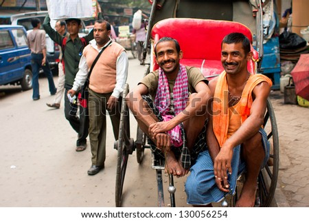 "KOLKATA, INDIA - JAN 21: Two workers of hand-pulled rickshaw smile during the relax hour on the street on January 21 2012. Kolkata's ""road space"" was only 6% compared to 23% in Delhi & 17% in Mumbai - stock photo"