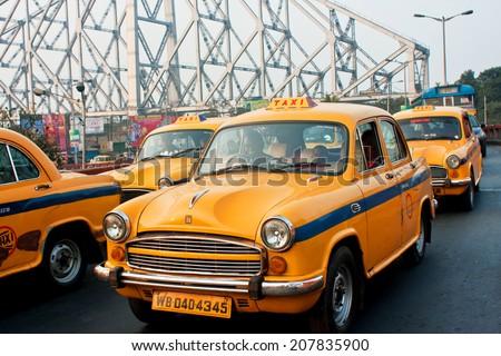 KOLKATA, INDIA - JAN 19: Yellow taxi cabs stop in traffic jam street with metal bridge background on January 19, 2013 in Kolkata, India. Kolkata has a density of 814.80 vehicles per km road length  - stock photo