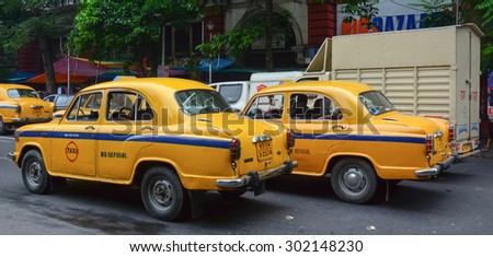 KOLKATA, INDIA - JUL 8, 2015. Yellow Ambassador taxi cars go on the street in Kolkata, India. First Ambassador was produced by the Yellow Cab Manufacturing Company in 1921. - stock photo