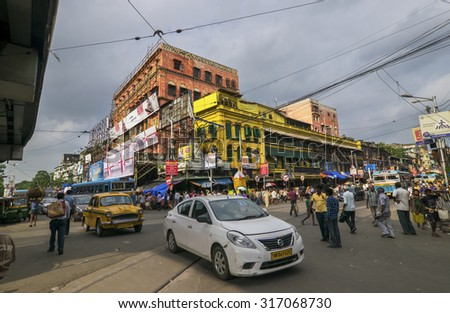 KOLKATA , INDIA - JULY 18, 2015 : Ancient buildings and busy traffic of Kolkata street. Kolkata is 300 year old city with a large population using modern cars and latest amenities. - stock photo