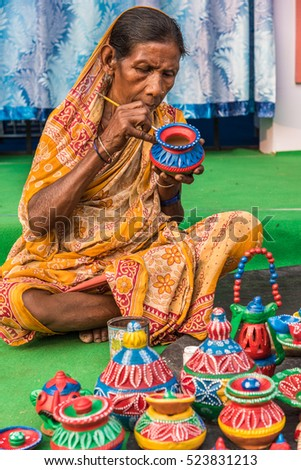 KOLKATA, INDIA - NOVEMBER 26: A rural craftswoman paints on colorful handicraft items for sale during the annual State Handicrafts Expo 2016 on November 26, 2016 in Kolkata, West Bengal, India.