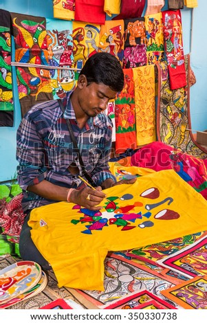 KOLKATA, INDIA - NOVEMBER 28: An Indian artisan paints on colorful handicraft items for sale during the annual State Handicrafts Expo 2015 on November 28, 2015 in Kolkata, West Bengal, India. - stock photo