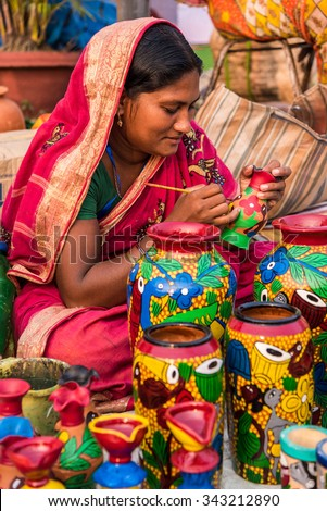 KOLKATA; INDIA - NOVEMBER 24: An Indian craftswoman paints on colorful handicraft items for sale during the annual State Handicrafts Expo 2015 on November 24; 2015 in Kolkata; West Bengal; India. - stock photo
