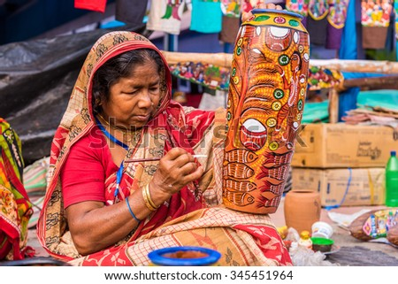 KOLKATA, INDIA - NOVEMBER 28: An Indian elderly craftswoman paints on colorful earthen vase for sale during the annual State Handicrafts Expo 2015 on November 28, 2015 in Kolkata, West Bengal, India. - stock photo