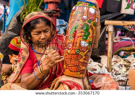 KOLKATA, INDIA - NOVEMBER 28: An Indian elderly craftswoman paints on colorful handicraft items for sale during the annual State Handicrafts Expo 2015 on November 28,2015 in Kolkata,West Bengal,India - stock photo