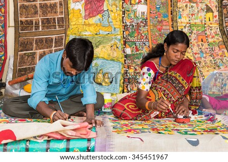 KOLKATA, INDIA - NOVEMBER 28: Indian artist couple paint on colorful handicraft items for sale during the annual State Handicrafts Expo 2015 on November 28, 2015 in Kolkata, West Bengal, India.