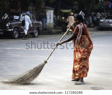 KOLKATA, INDIA - OCT 06, 2011: An unidentified woman in bright colorful sari sweeps along Park Street  with long broom during Durga Puja on October 06, 2011 in Kolkata, India. - stock photo