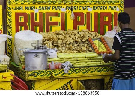 KOLKATA, INDIA - OCTOBER 02: A small roadside stall holder sells Bhel Puri, a popular local snack, during Hindu festival of Durga Puja on October 02, 2011 in Kolkata, Bengal, India, - stock photo