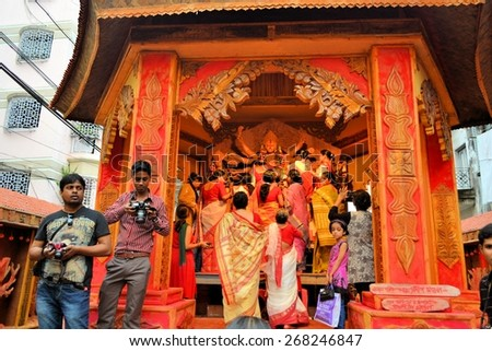 Kolkata, India - 14 October 2013:  Devotees at an idol of revered goddess Durga standing in an unidentified pandal in the city of Kolkata during Durga Puja festival. A pandal is a temporary temple