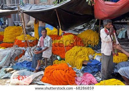 KOLKATA, INDIA - 27 OCTOBER: Indian flower vendors offer their items on flower market in Kolkata on October 27, 2009. The Kolkata flower market is known as eastern India's largest flower market. - stock photo