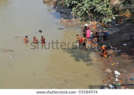 KOLKATA, INDIA - OCTOBER 27: Indian people wash themselves in Hooghly River on October 27, 2009 in Kolkata, India. At present time this river, like the others in India, is being polluted tremendously. - stock photo