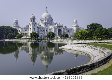 Kolkata, India - The Victoria Memorial on a bright sunny morning with blue sky with reflections of the memorial in the water feature to the front of the monument.
