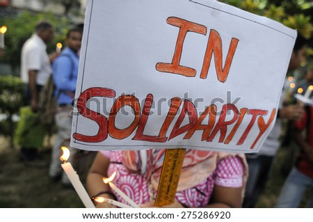 """KOLKATA - MARCH 16 : A woman with a """"solidarity"""" sign while her face is hidden during a candle light vigil to protest gang rape of an elderly nun on March 16, 2015 at Allen Park in Kolkata, India. - stock photo"""