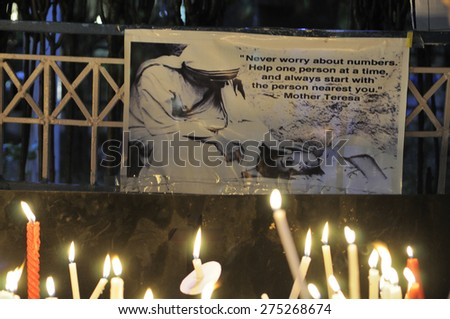 KOLKATA - MARCH 16 : Burning candles in front of an image of Mother Teresa during a candle light vigil to protest gang rape of an elderly nun on March 16, 2015, at Allen Park in Kolkata, India. - stock photo