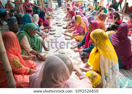 "KOLKATA- NOVEMBER 6: Women volunteers collectively making ""roti""during a Langar or community kitchen service which in Sikhism refers to free meal for all  on 6th November, 2014 in Kolkata, India"