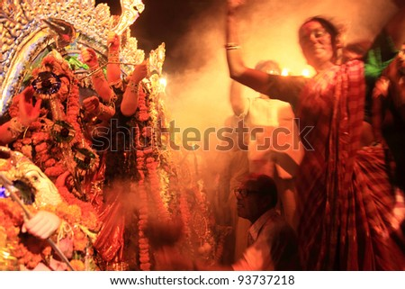 KOLKATA - OCT 17: Devotees dance in front of huge Durga idol before immersion during Durga Puja festival on October 17, 2010 in Kolkata, India. Durga puja is the biggest festival in West Bengal, India - stock photo