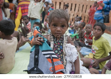 KOLKATA - OCTOBER 26 :A girl child of a brick worker with donated clothes hanging to her shoulder on October 26, 2014 in Kolkata , India.  - stock photo