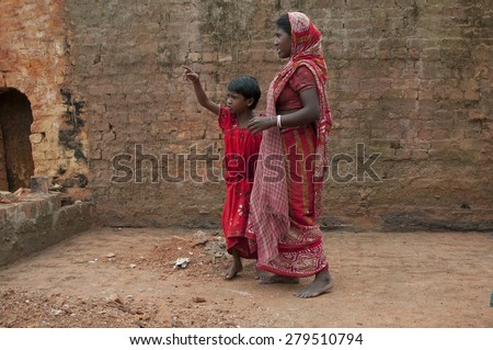 KOLKATA-OCTOBER 26: A girl child talking to her mother inside a brick factory where they work and stay for minimum wage and unhealthy living conditions on October 26, 2014 in Kolkata,India. - stock photo