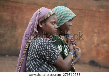 KOLKATA - OCTOBER 26 : A teenage girl embracing her friend inside a brick factory where they and their family work under tough and unhealthy conditions on October 26, 2014 in Kolkata , India.  - stock photo